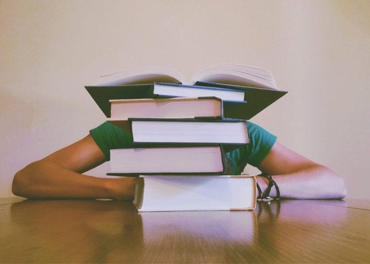 persoon verborgen achter boeken