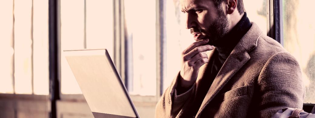 Man met hand op zijn kin met laptop