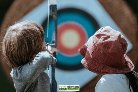 Kind met boog en pijl voor een doel