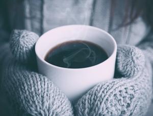 warme tas koffie in handen met wanten
