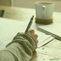 Hand met pen schrijft op papier