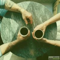 Tafel met twee paar handen die een koffie vasthouden