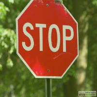 Stopbord in de straat op een groen achtergrond