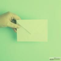 Hand die een enveloppe vasthoud op een blauwe achtergrond