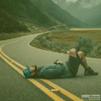 Man met pet ligt midden op de weg