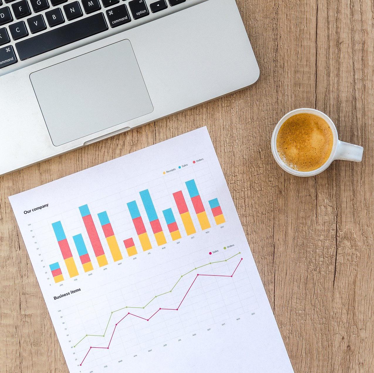 Computer met tas koffie en blad met grafieken
